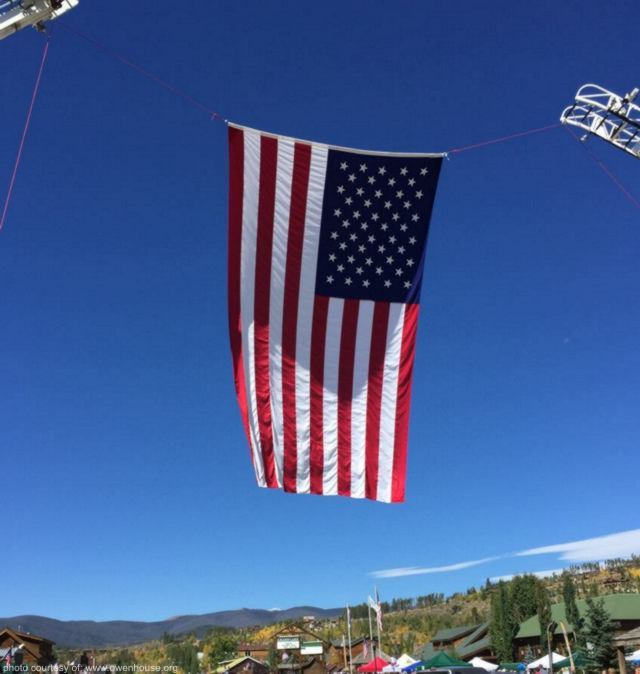 This is a picture facing west down Grand Avenue in downtown Grand Lake, Colorado with a hugh USA Garrison Flag hanging between two firetrucks on Parade day during Constitutin Week.