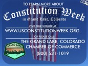 A thumb nail view of Grand Lake, Colorado during Constitution Week in September looking at the Town Park Sign and the Garrison Flag that hangs over Grand Ave. on parade day with inforomation on how to contact the Grand Lake Chamber of Commerce; click here to open a window with a larger picture.