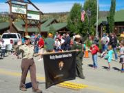 A thumb nail view of Grand Lake, Colorado during Constitution Week in September looking at two (2) Park Rangers carrying the Rocky Mountain National Park Banner in the Parade; click here to open a window with a larger picture.