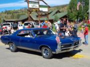 A thumb nail view of Grand Lake, Colorado during Constitution Week in September looking at a vintage blue car rolling down Grand Avenue in the parade; click here to open a window with a larger picture.