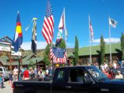 A thumb nail view of Grand Lake, Colorado during Constitution Week in September looking at a small black truck with several flags, with the town park sign and flags in the background; click here to open a window with a larger picture.